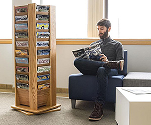 A wooden magazine rack shown inside a commercial lobby