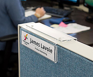 A cubicle name plate hanger shown in an office environment