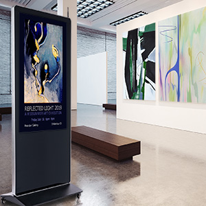 A digital floor stand displaying information inside an art gallery