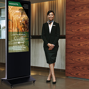 A hotel hostess standing next to a digital floor sign detailing a rewards club program