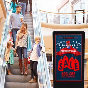Shoppers in a mall looking at a digital floor sign advertising a sale