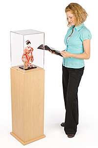 Woman standing next to a display case pedestal