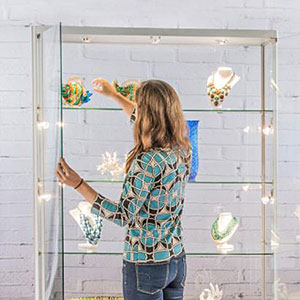 Woman stocking a commercial extra wide display case with merchandise