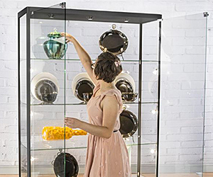 Woman placing a bowl onto a shelf inside a floorstanding glass display case