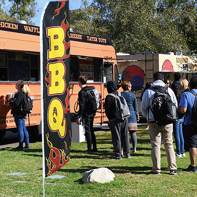 People lining up for food truck service next to a BBQ feather flag at an outdoor festival
