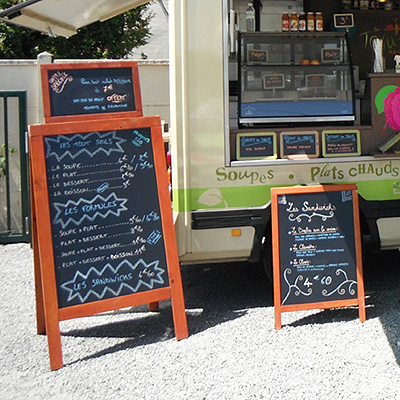 Food truck shown with A-frame chalkboard signs