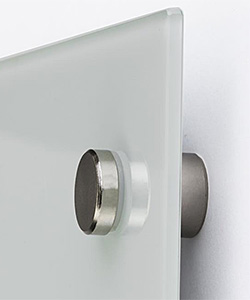 Closeup of a glass whiteboard mounted with wall standoffs