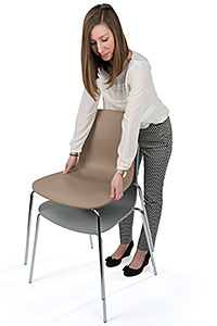 Woman stacking two modern designer chairs