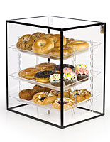 This acrylic pastry display case features black metal framing for stability and stylish accents.