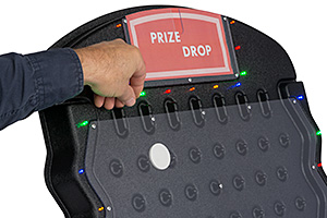 Closeup of person dropping a puck into a prize drop board