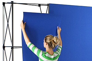 Woman shown attaching receptive fabric panels to a pop-up wall display