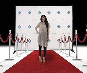 Woman standing on a red carpet  in front of a step & repeat photo backdrop