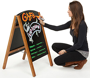 Girl writing a new message on a sidewalk markerboard