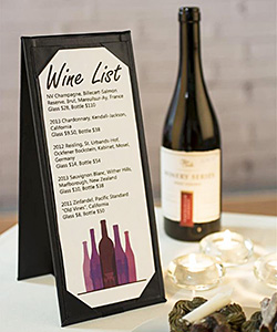 A tent card holder displaying a wine list on a restaurant table