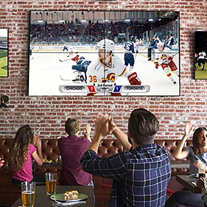 Patrons inside a restaurant cheering to a sports game on a large video wall installation