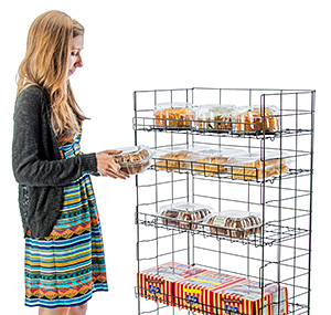 Girl selecting baked goods from a wire display shelf