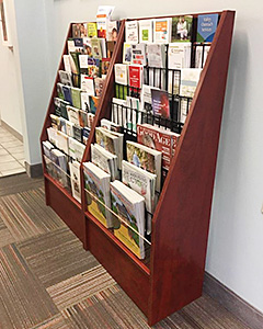 A waiting room shown with a wooden brochure stand