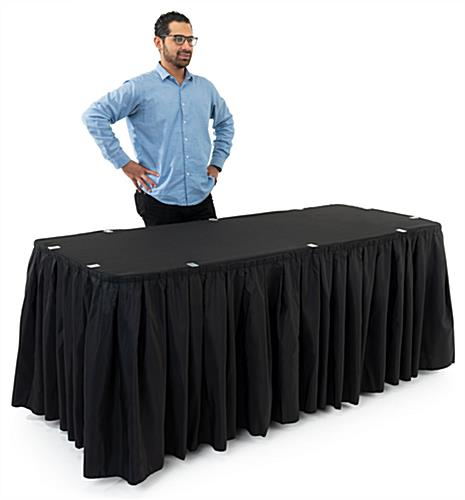 Man with glasses standing behind black table linens