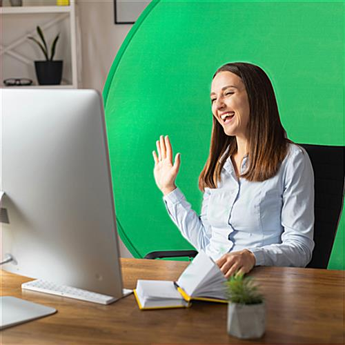 Woman sitting at desk with green screen background