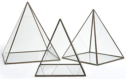Medium glass pyramid display case with gold metal pipping along edges