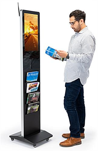Man standing at a magazine rack digital display reading from a periodical