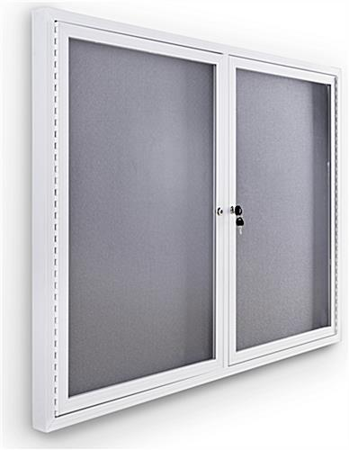 Indoor enclosed bulletin board cabinet with white frame and gray interior