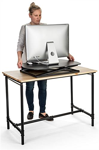 Standing desk converter riser holds computer equipment and other office essentials