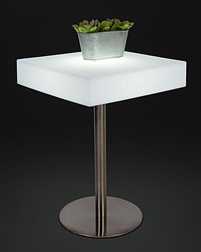 Square glow top bar table illuminated in white shown with a small planter
