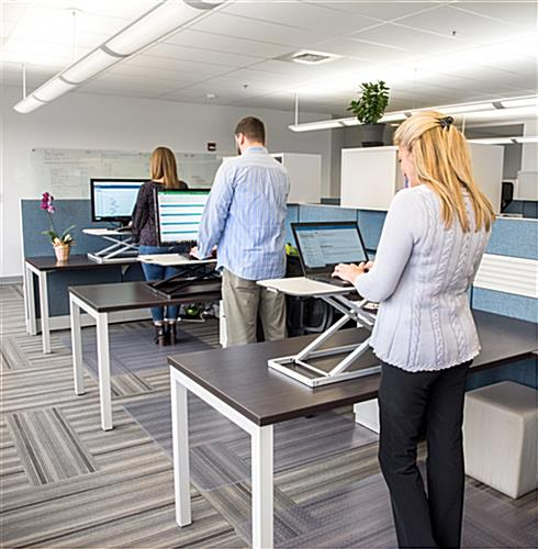 Height adjustable standing desk converter for office environments