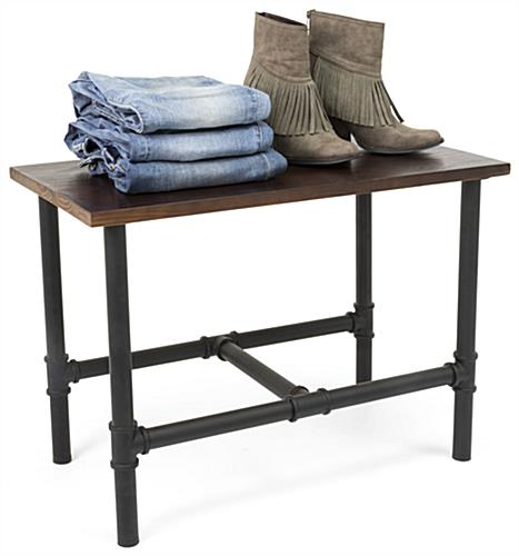 Small Pipe Display Table Showcasing Folded Jeans