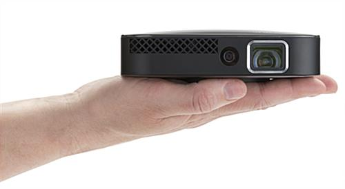 Portable mini projector shown in palm of hand for scale