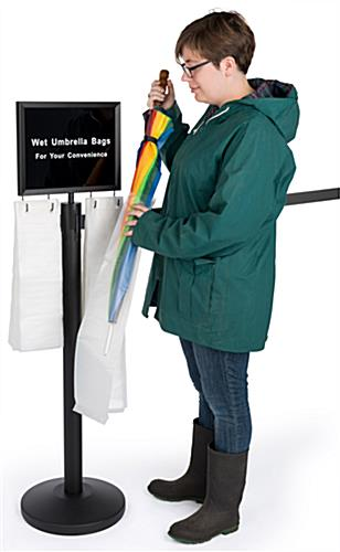 Gray belt stanchion umbrella station with courtesy bags for patrons