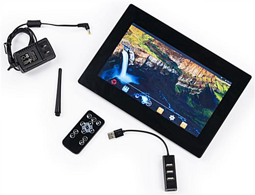 Small tabletop digital signage display featuring remote and USB extender
