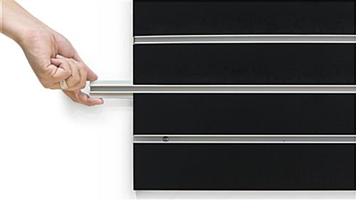 Person Removing Channel Insert of the Large Black Slat Board Display Panel